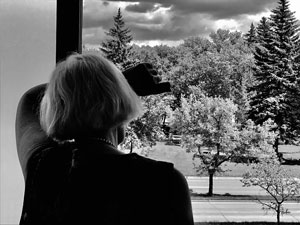 Woman standing alone looking out a window