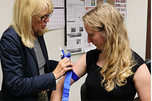 Dr. Mary Aaland, left, demonstrates applying a tourniquet on RHIhub writer Allee Mead.
