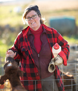 Meg Moynihan, MDA Senior Advisor of Strategy & Innovation, feeds a calf on her organic dairy farm.