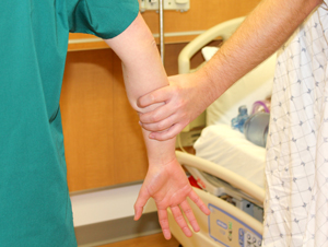 a healthcare worker's arm gripped tightly by a patient