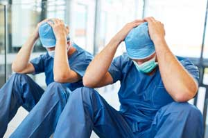 two exhausted surgeons with hands on head