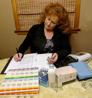 Maria Waters works on filling her parents med planners and tracking their medications.
