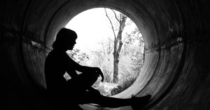 silhouette of a girl sitting in a sewer pipe